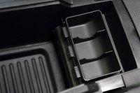 В боксе между сиденьем крепления для различных мелочей, розетка, аудио-выход