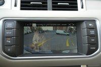 Восьмидюймовый тач-скрин на Evoque имеет функцию «двойного экрана», которая позволяет показывать разное изображение водителю и пассажиру. Видно, как на фоне изображения с камеры заднего вида ходит «привидение» с канала НТВ