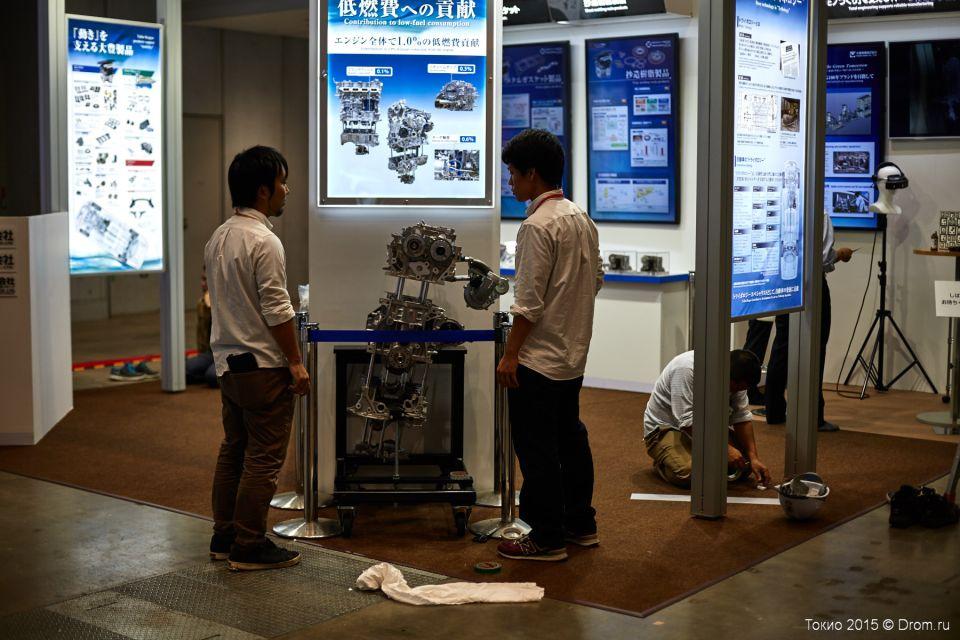 Японцы настраивают механическую модель двигателя.