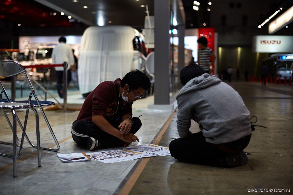 Японцы сидят на полу и обсуждают план монтажа конструкций павильона. Обратите внимание, что рядом с ними стоят два пустых стула.