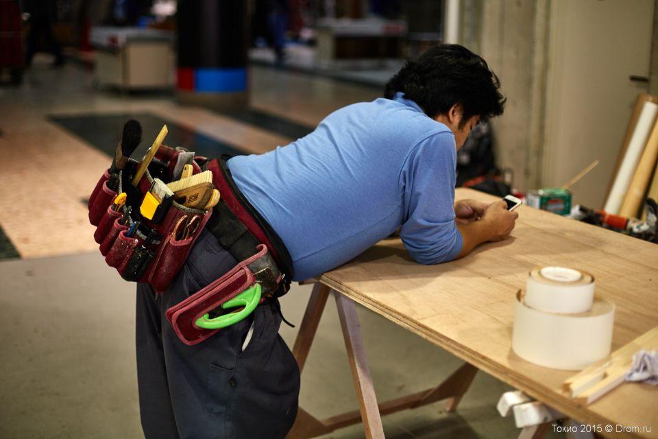 В свободную минуту рабочий японце, так как и мы, любит посмотреть в телефон. Пояс у него, конечно, профессиональный. Обзавидуешься.