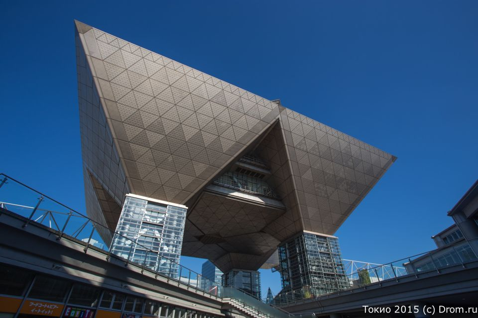 Токио Биг Сайт на искусственном острове Одайба — место проведения Токийского автосалона в последние несколько лет. Эта странная перевёрнутая усечённая пирамида на столбах — не работающий пресс-центр