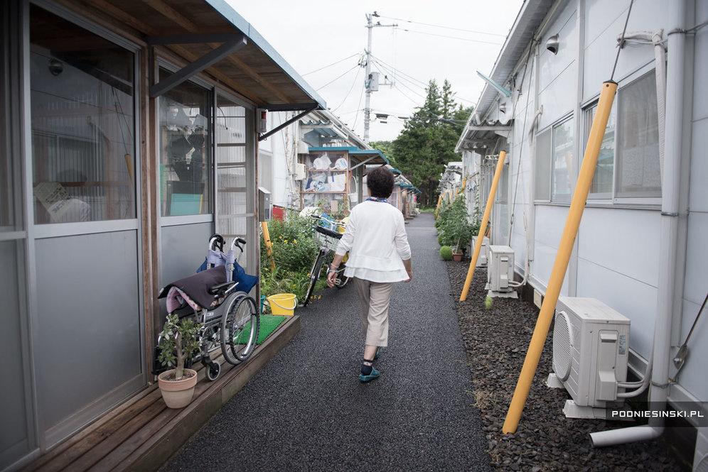 Йоуко Нодзава идет среди временных построек, в которых расположились бывшие жители зараженного региона